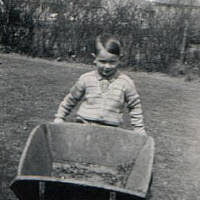 small boy playing with wheelbarrow 1950's